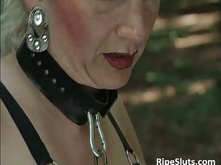 Mature blonde slut on a leash gets fucked in the forest