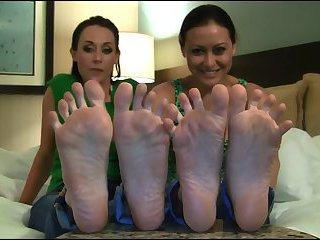 2 brunettes show soles on the bed