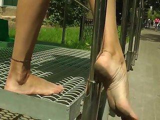 Brunette walks with dirty feet in public