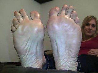 Blonde posing big feet on bed