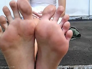 Girl in dress shows long dirty soles