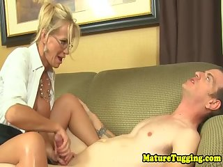 Spex cougar seduces young guy with handjob