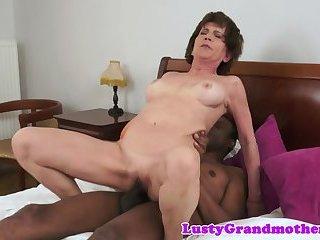 Busty grandma enjoys in interracial action