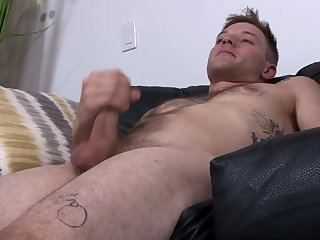 Tattooed stud solo wanking on the sofa