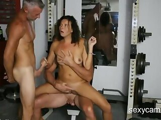 Slutty MILF having some fun with two guys in the gym live at sexycamx.com